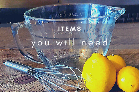 Glass measuring cup with a whisk and three yellow lemons on rustic boards with the words what you will need