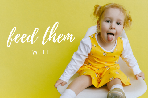 A little girl in a yellow dress and a white long sleeve shirt sitting on a chair and sticking her tongue out with the words feed them well