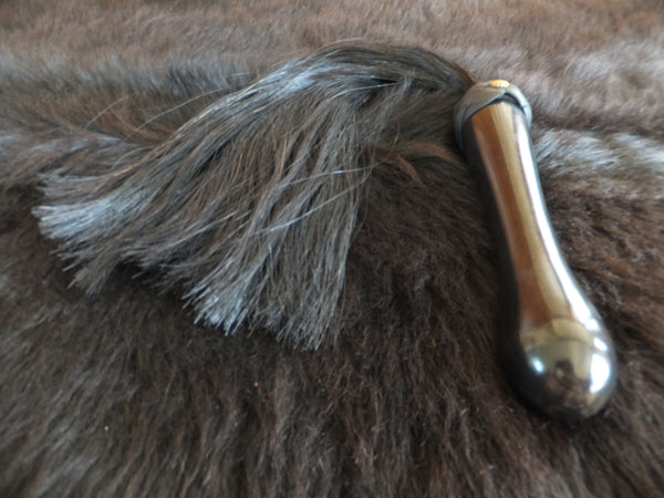 Horse hair attached to a hand-crafted turned wood handle.