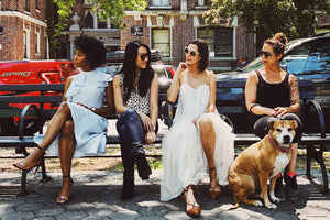 Four women sit on a bench. One of them has a dog sitting by them on the ground.