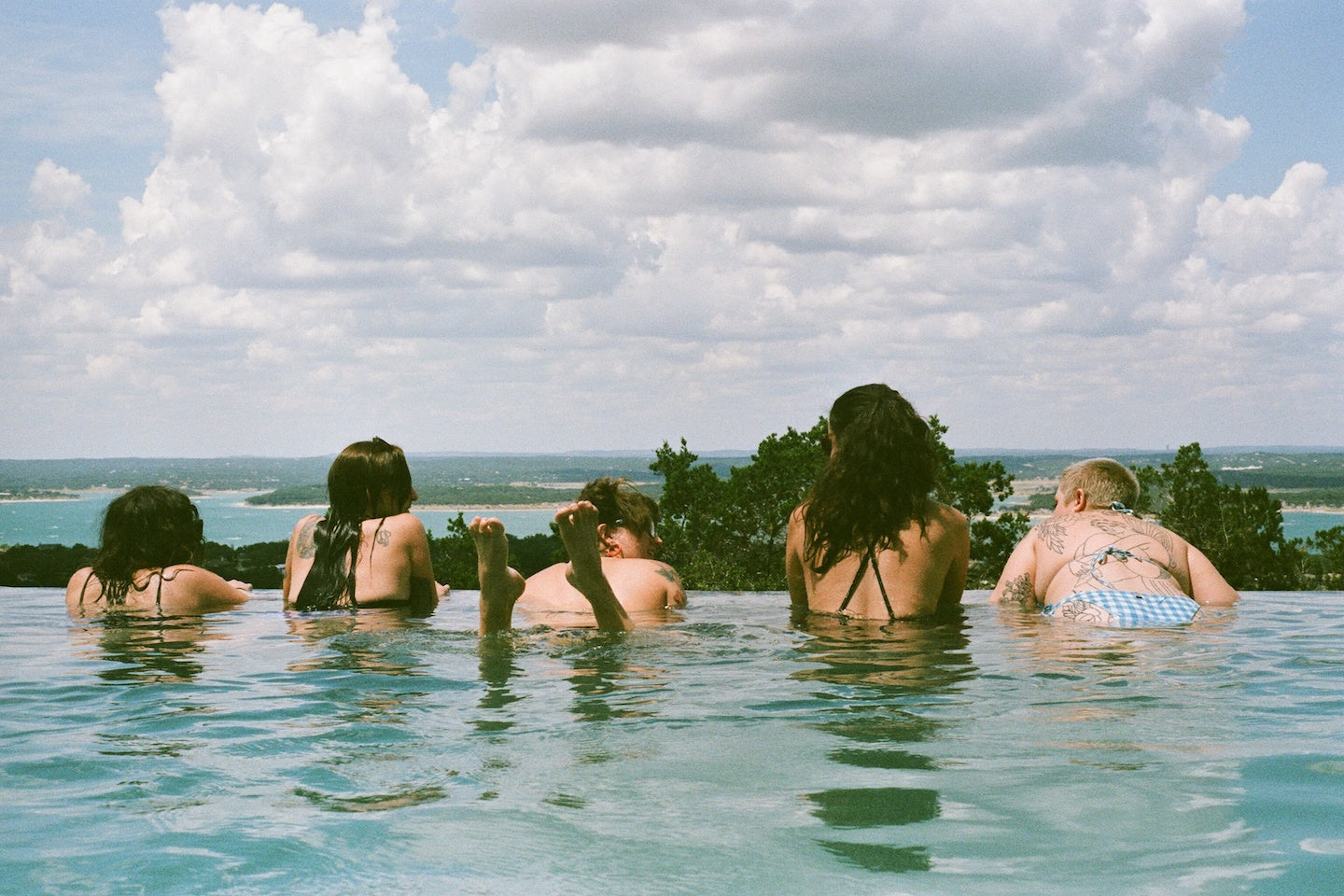 Five people in swimsuits in a pool looking out to the horizon. You can see trees, water, and sand in the distance