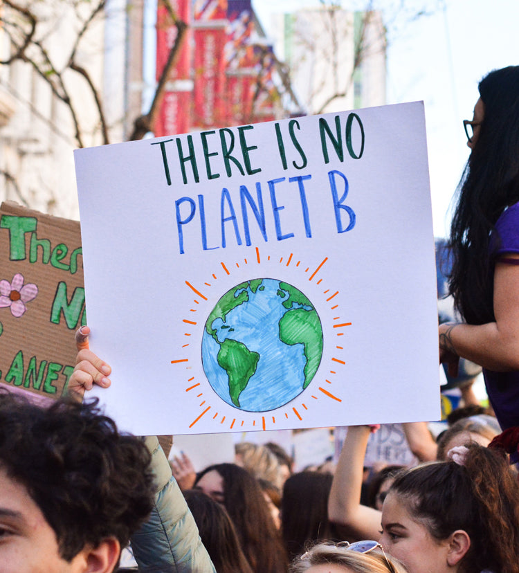 "A sign is held up at an environmental protest. The sign reads ""There is no Planet B"" and has a drawing of the earth on it."