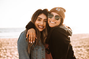 Two women on the beach, smiling at the camera