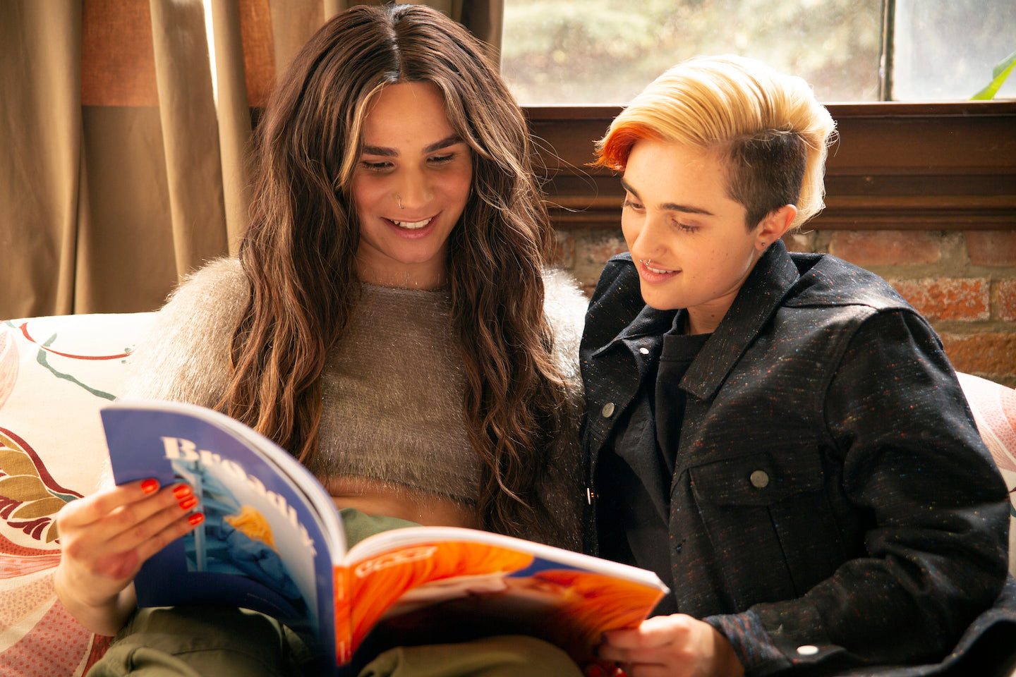 A transfeminine non-binary person and transmasculine gender-nonconforming person reading a magazine together.