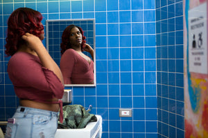 A young transgender woman looking in a bathroom mirror.