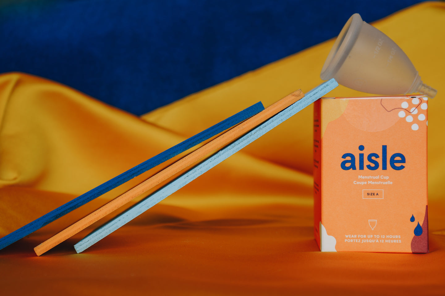 An Aisle menstrual cup sits on top of its box. There are 3 thin rectangular pieces of wood leaning up against the cup box.