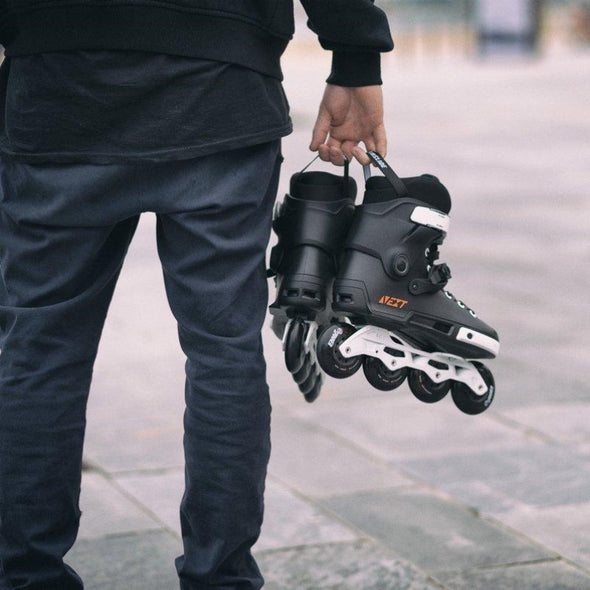 man holding the powerslide next black 80mm inline skates
