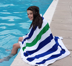 girl at the pool, striped beach towel over her shoulders