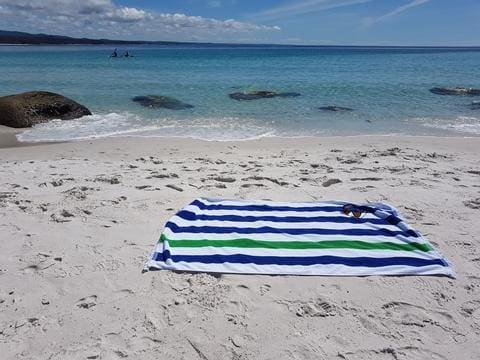 striped beach towel in white sand with sunglasses and blue sea in the background