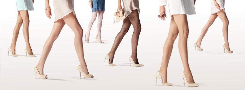 Several legs walking forward wearing sheer hosiery and with the bottom part of their dresses showing, all women are wearing cream high heeled shoes.