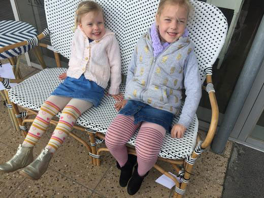 Two younger girls sitting happily wearing bright coloured tights.