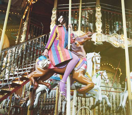 Lady astride a carousel horse wearing brightly coloured clothes.