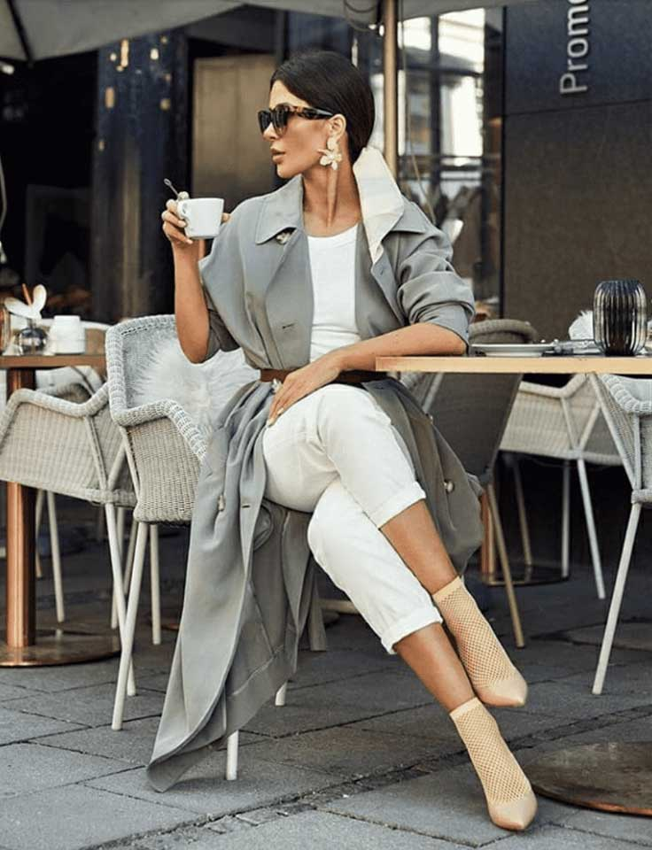 An elegantly dressed lady sitting at and outdoor cafe, sipping an espresso