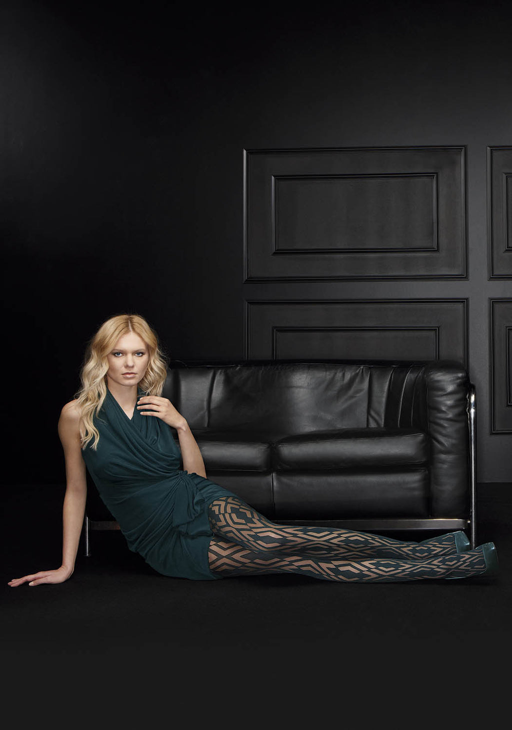 Blonde lady sitting side on with legs outstretched wearing a short green dress and green tights.