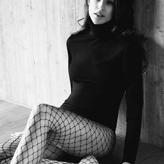 Lady sitting and wearing a black turtle neck top with Oroblu Glamour fishnet black tights on her legs.