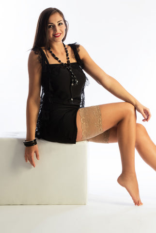 Lady sitting in nude lace thigh bands that prevent thigh chafing.