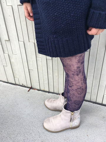 A young girls' legs displaying floral tights in a royal blue colour.