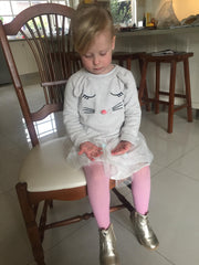 Little girl sitting perched on a chair in a white tutu and pink stockings.