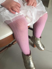 Close up of little girls lower legs wearing pink tights.
