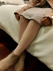 Close up of a girl's lower leg wearing ivory micro mesh tights.