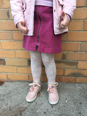 Child's lower body, standing against a wearing various shades of pink.