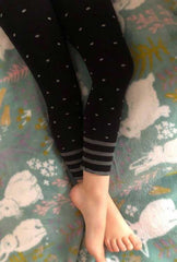 Girl's legs outstretched on a bed wearing black leggings with grey spots.