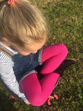 Little blonde girl sitting on the grass with her legs crossed in bright pink tights.