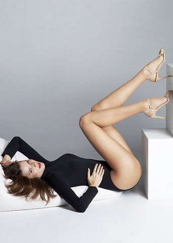 Girl lying down with legs in the air wearing Divine 10 nanofiber tights by Oroblu