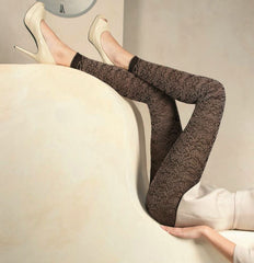 Lady's legs upright resting on a sofa back in brown lace footless tights and cream shoes.