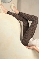 Side view of lady's legs up agains a couch in brown and black footless tights.