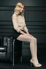 Blonde lady sitting side on wearing a soft almond blouse, black skirt and beige tights.