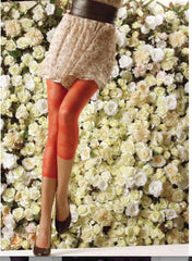 Lady's legs in orange footless tights, floral skirt and black shoes, standing in front of a floral wall.