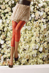 Lady's legs standing in black heels, orange footless tights and a floral skirt.