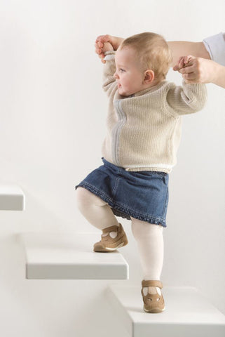 Baby girl being held by the hands up in the air and guided as she walks up a step.