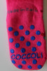 Coccoli pink grip socks displaying blue grips on back sole.