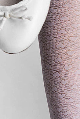Close up of girl's leg wearing white sheer heart pattern tights against a white ballerina shoe.