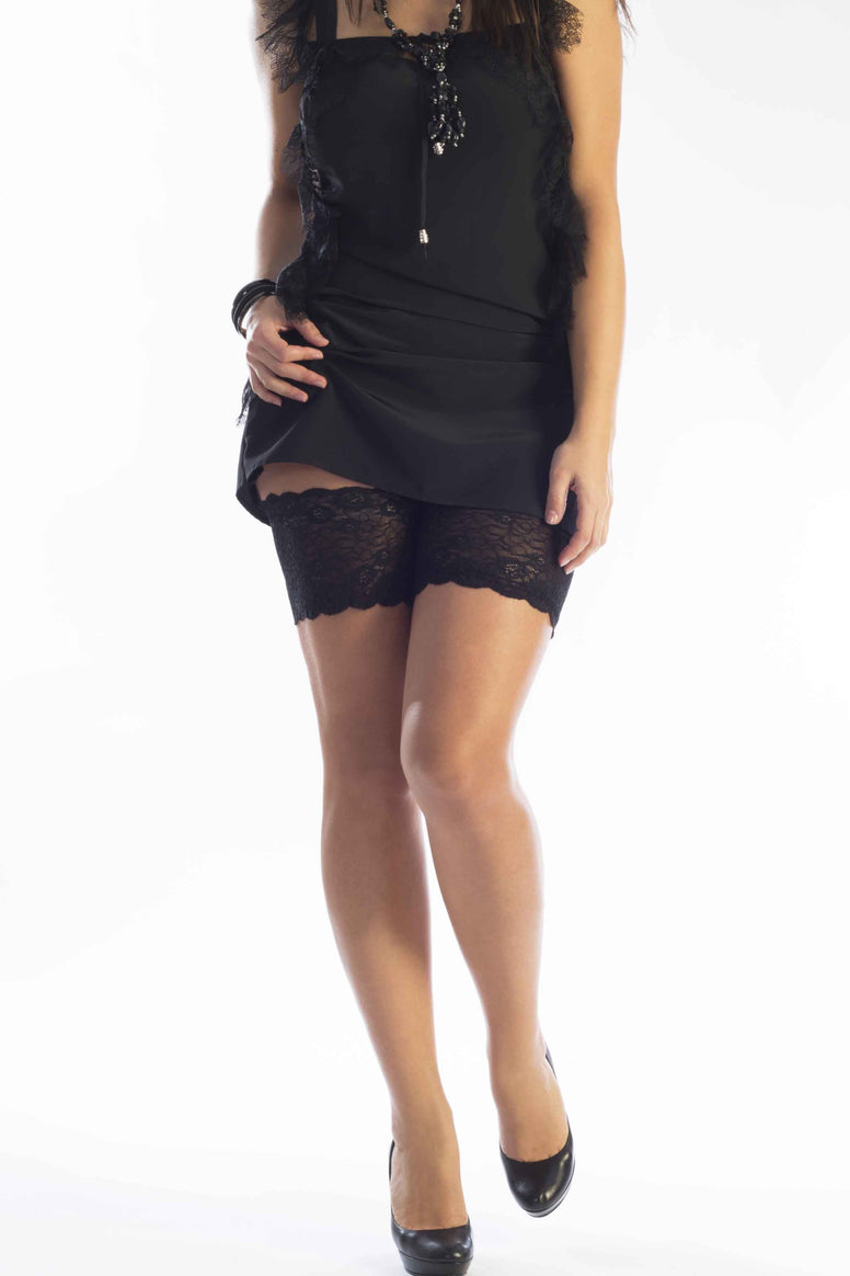 Lady walking wearing black clothing showing black lace thigh bands on upper legs.