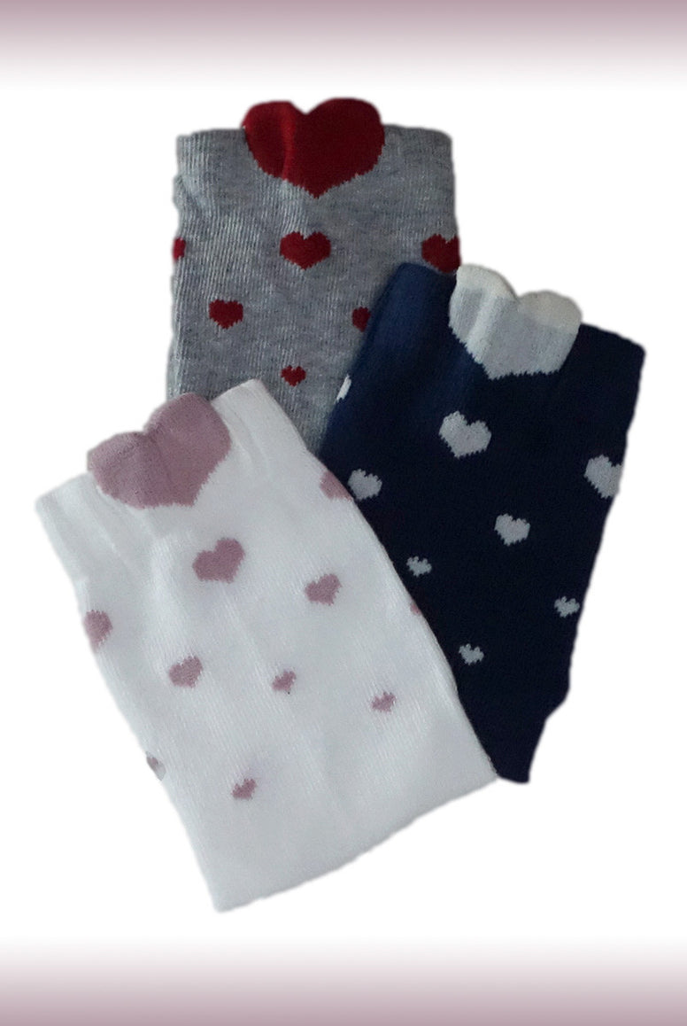 Three pairs of Coccoli Children's socks in navy, white and grey with heart prints.