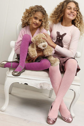 Two girls sitting on large armchair holding and caressing a stuffed toy dog.