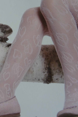 Close up of girls' legs in a sitting position wearing heart pattern lace mesh tights.