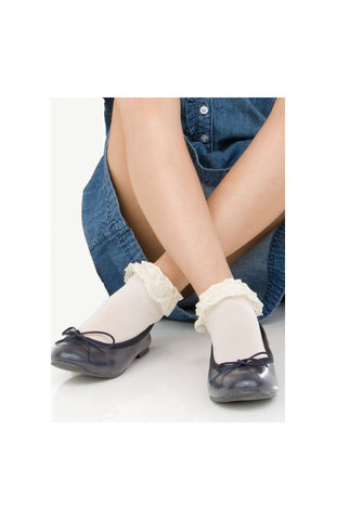 Girl's legs crossed at the ankles wearing a blue denim dress and white frilly ankle socks in black ballerina flats.