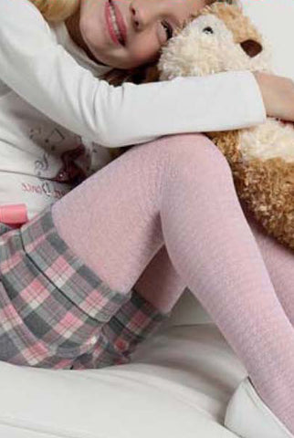 Close up of girls leg ,pulled up with arm resting on her leg, wearing cheque shorts and pink tights with a houndstooth pattern.