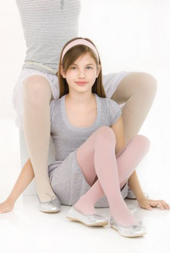 Girl sitting with legs crossed on the floor in between her mother's legs.