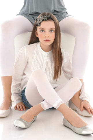 Young girl sitting with legs crossed in white lace footless tights and ballerina flats.