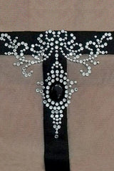 Close up sparkling crystals on black tattoo effect motif to form pendant style decoration
