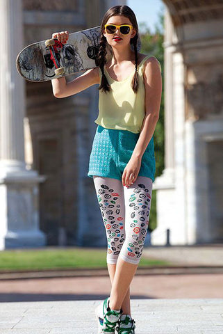 Teen girl standing with skateboard on her shoulders legs crossed at ankles, wearing white Fable floral capri footless tights.