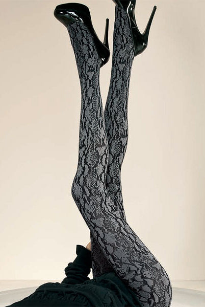 Lady's legs upright in the air wearing grey black snake pattern tights with black stiletto shoes.