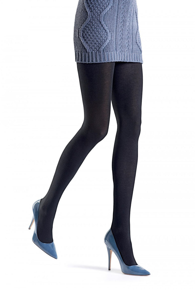 Close up of front side view of lady's legs walking and wearing plain knit Tessie Oroblu black tights in grey high heeled shoes. Some of her long cable knit grey jumper can also be seen.
