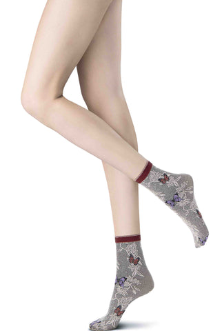 Side view of lady's legs and feet wearing butterfly print short socks.