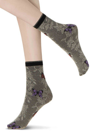 Close up of lady's feet in short coloured ankle socks with butterfly print.